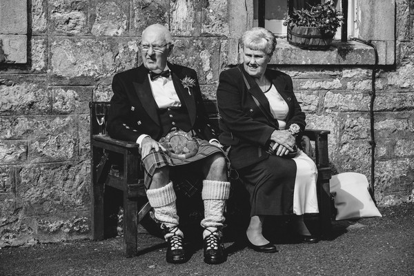 Man in kilt sitting on bench at wedding