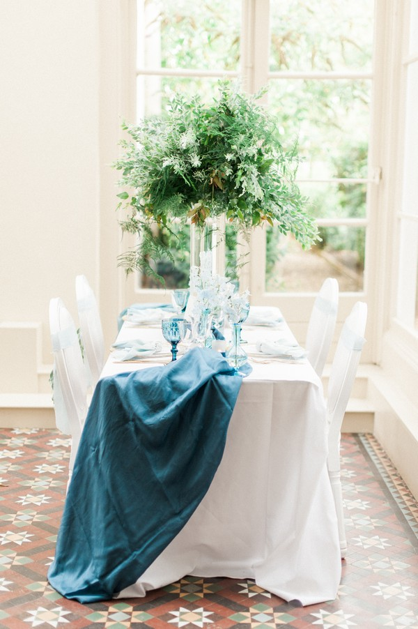 Long wedding table with Blue runner and large foliage centrepiece