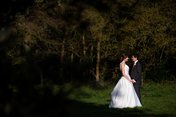 Bride and groom facing each other in garden at Kings Weston House