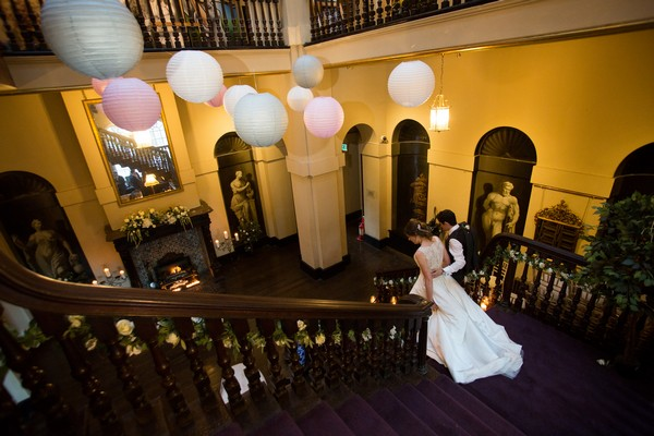 Bride and groom walking down stairs at Kings Weston House
