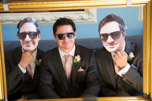 Groom with groomsmen wearing masks of his face