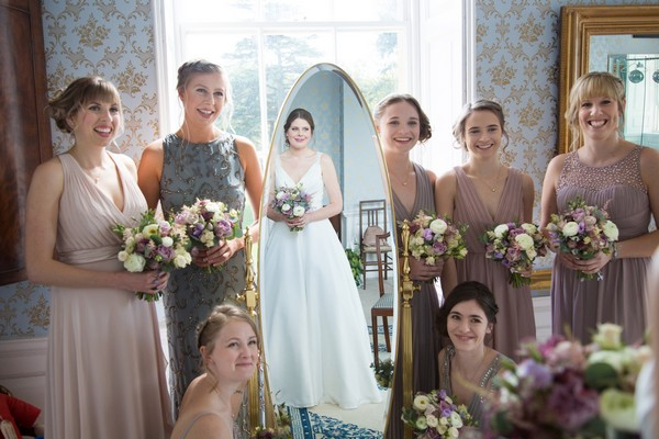 Bridesmaids standing next to mirror with bride's reflection