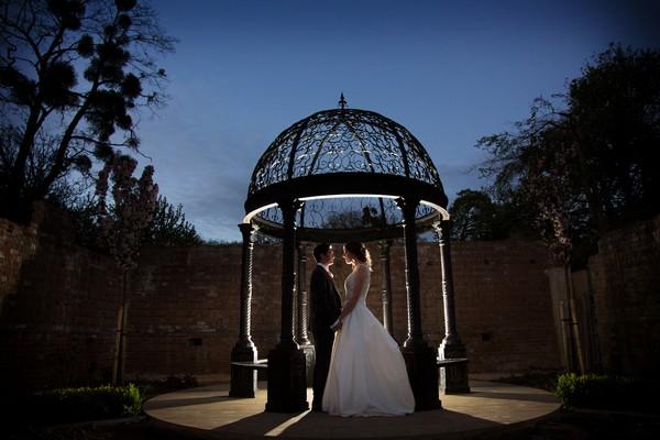 Bride and groom by gazebo at Kings Weston House