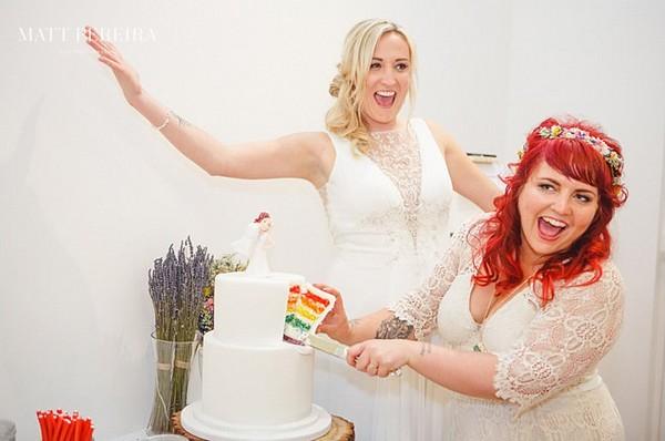 Bride's cutting rainbow wedding cake