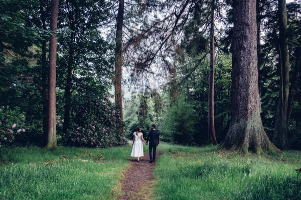 Bride and groom walking towards woodland