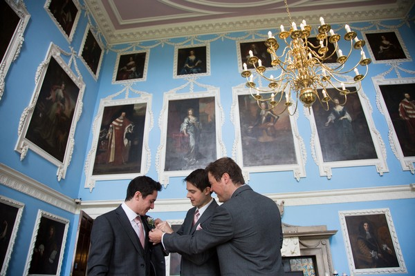 Groomsmen adjusting groom's buttonhole at Kings Weston House