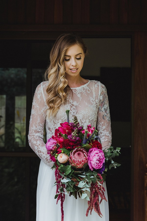 Bride in lace crop top holding bouquet