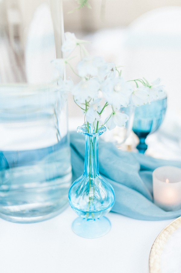 Small blue vase of flowers on wedding table