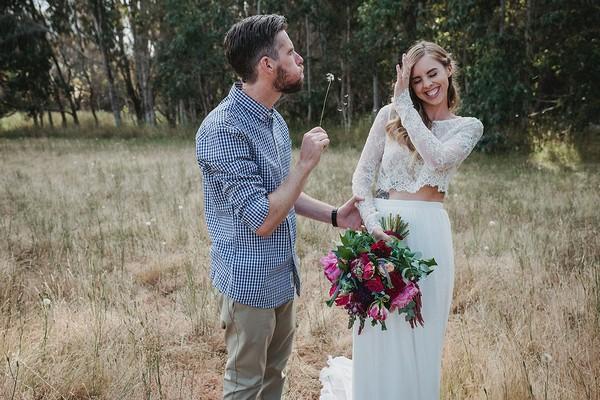 Groom blowing dandelion as bride