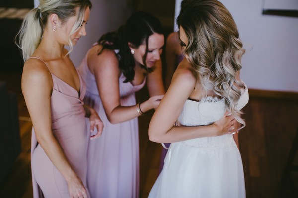 Bridesmaids doing up back of bride's wedding dress