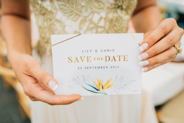 Bride holding tropical styled wedding save the date