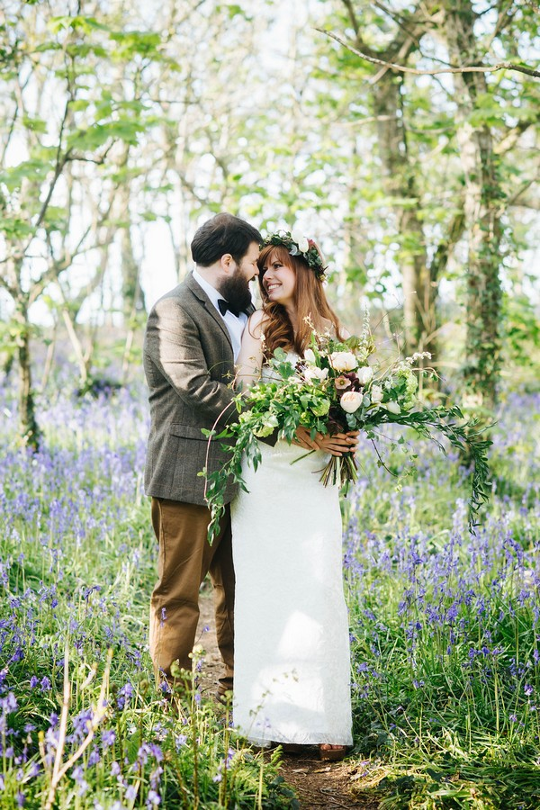 Couple standing in bluebells in woodland
