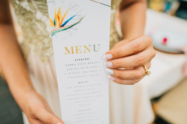 Bride holding tropical styled wedding menu