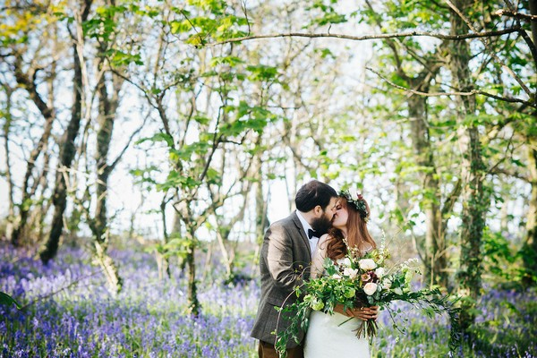 Couple kissing in bluebells in woodland