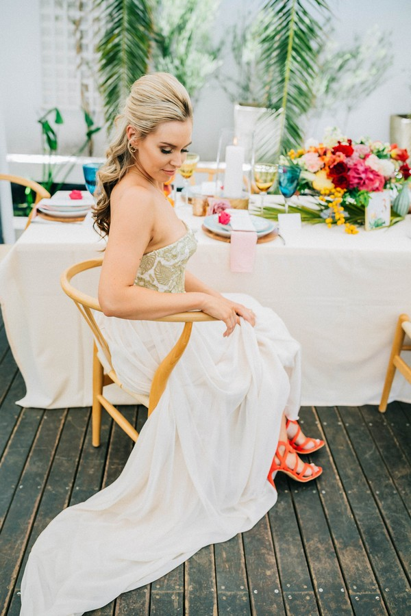 Bride sitting next to wedding table