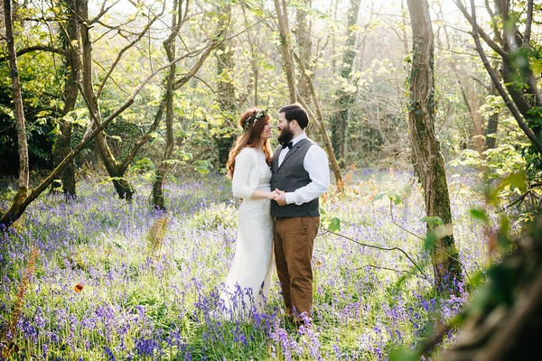 Bride and groom standing in bluebells