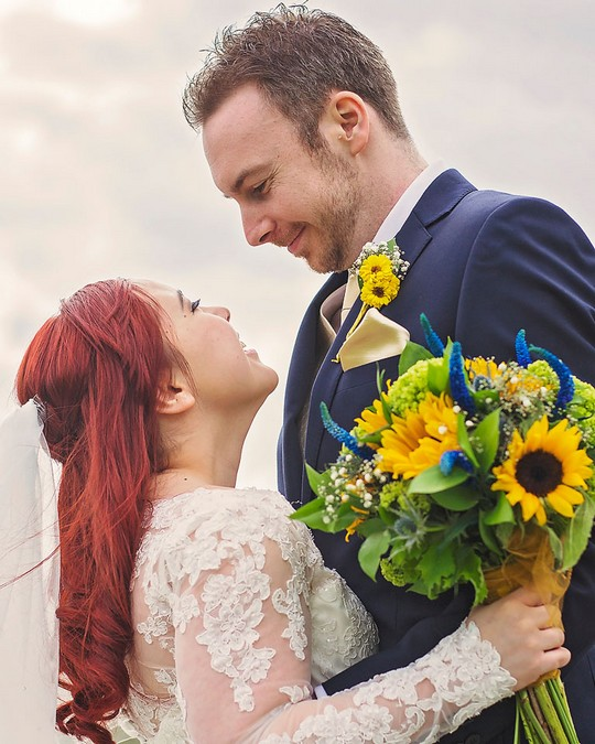 Bride with sunflower wedding bouquet looking into groom's eyes - Picture by Rebecca Gurden Photography