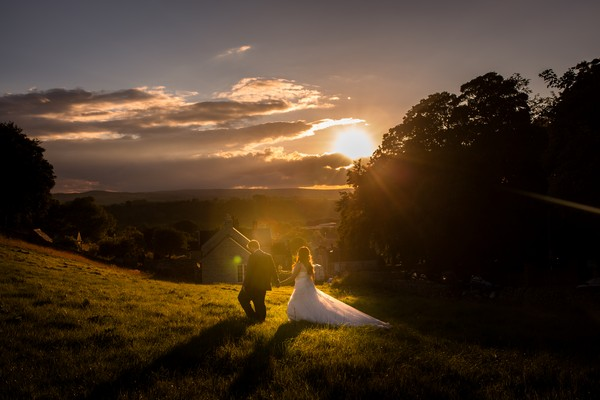 Bride and groom walking across hill as sun sets - Picture by Morgan Rana Photography