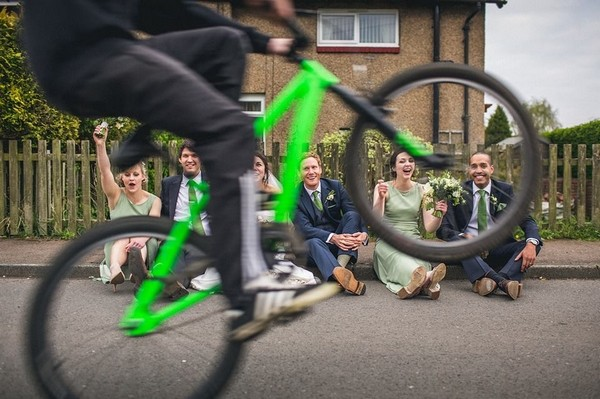 Bridal party sitting watching someone pull a wheelie on a bicycle - Picture by Andy Hudson Photography