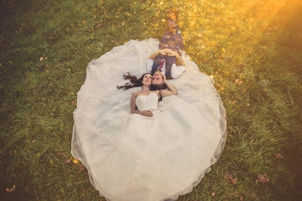 Bride and groom laying on bride's dress on grass - Picture by Him and Her Wedding Photography