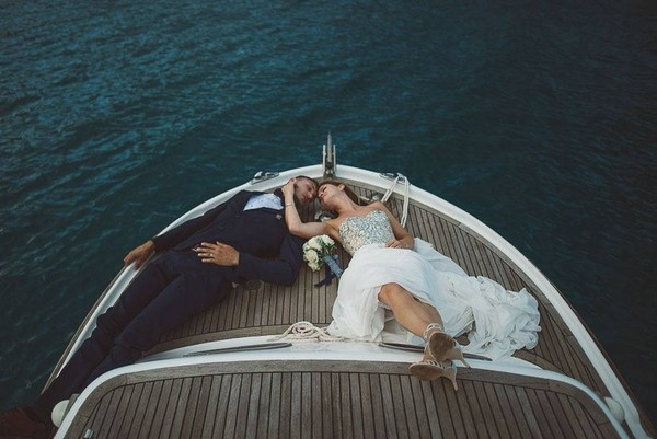 Bride and groom laying on front of a boat - Picture by Katja & Simon Photography