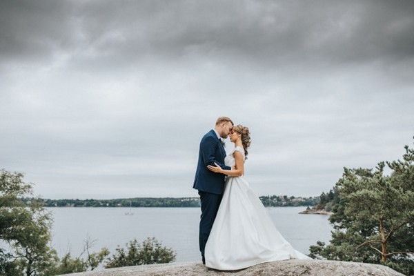 Bride and groom touching heads on rock in front of the sea - Picture by Anette Bruzan Photography