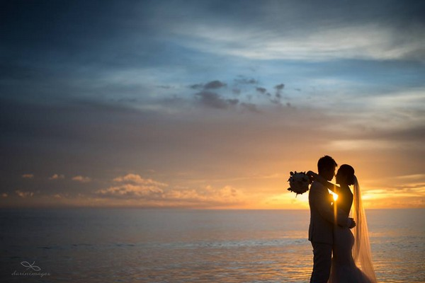 Silhouette of bride and groom in front of the sea with sun shining between them - Picture by darinimages
