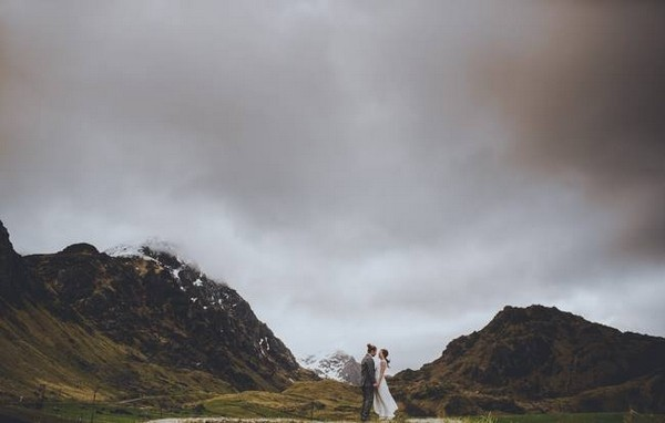 Bride and groom standing between two mountains - Picture by Steve Fuller Photography