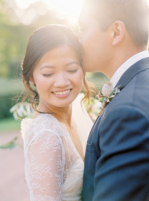 Bride smiling with eyes shut as groom kisses her on the head - Picture by 2 Brides Photography