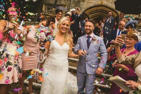 Bride and groom holding hands as guests throw confetti - Picture by The Springles