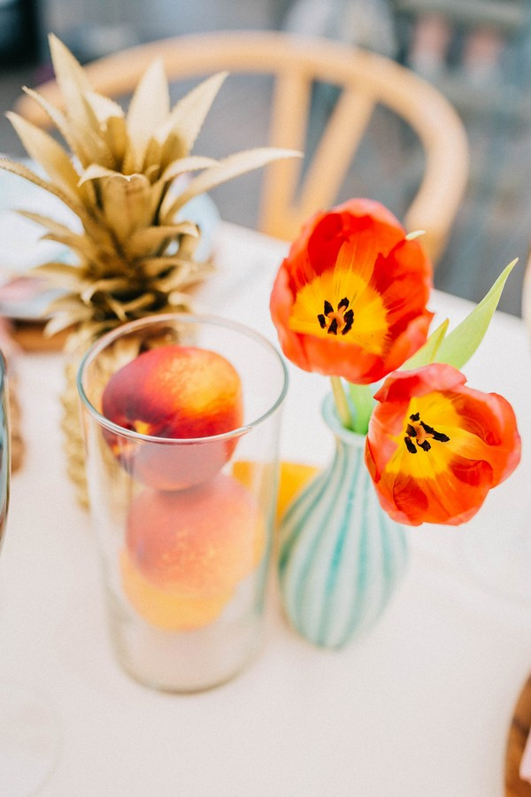 Bright orange flowers and fruit on wedding table