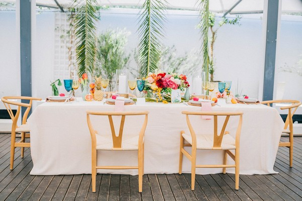Tropical styled wedding table with palm leaves backdrop