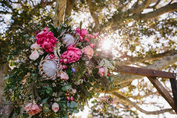 Large floral bouquet tied to wedding ceremony structure
