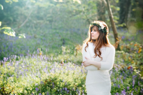 Bride with flower and foliage crown standing in woodland