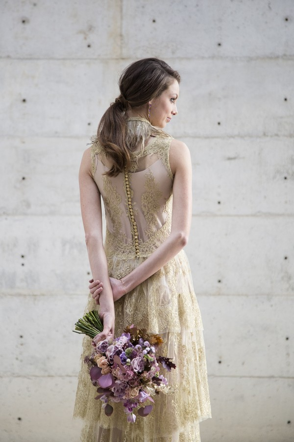 Bride in gold wedding dress holding purple bouquet behind her back