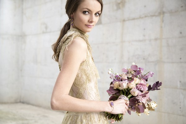 Bride in gold wedding dress holding purple bouquet
