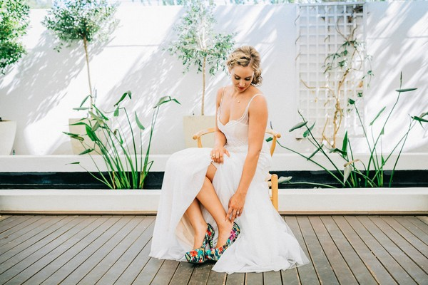 Bride looking down at colourful shoes
