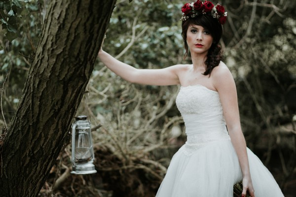 Bride leaning against tree