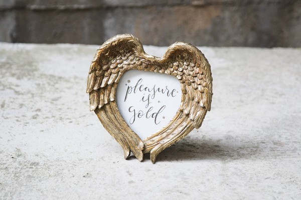 Pleasure is gold sign in gold feather heart frame