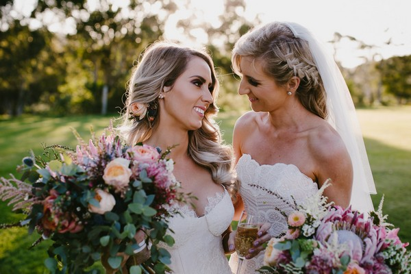 Two brides smiling at each other