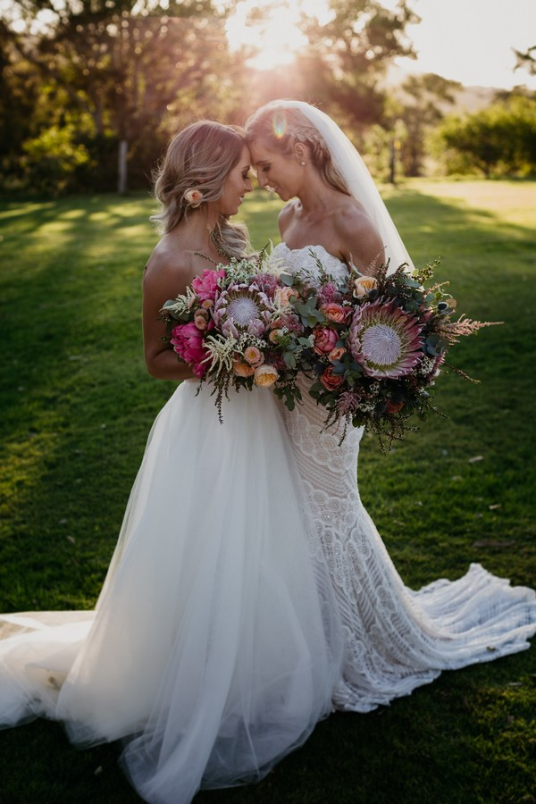 Two brides touching heads