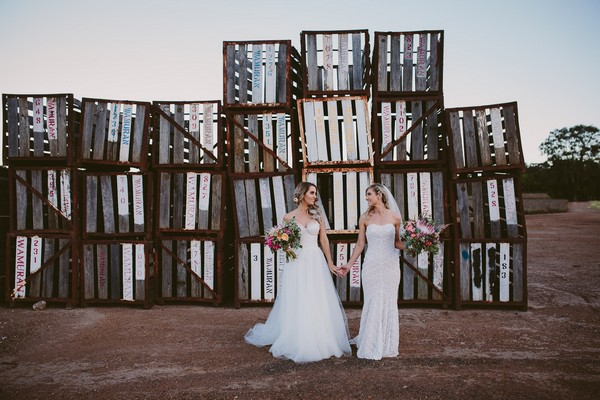 Two brides in front of old pallets