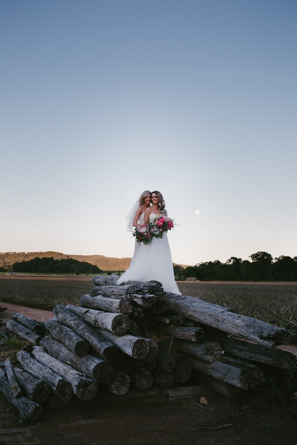 Two brides standing on pile of logs