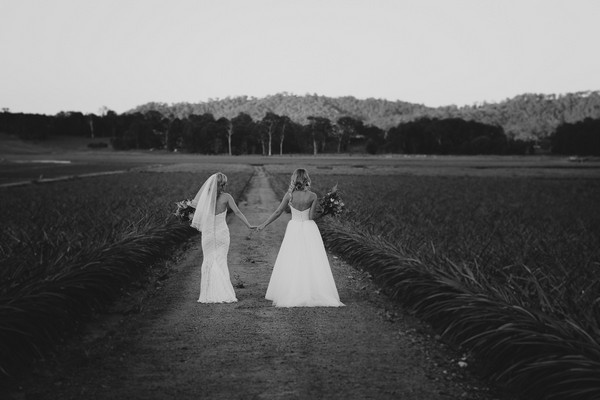 Two brides walking in grounds of Yandina Station