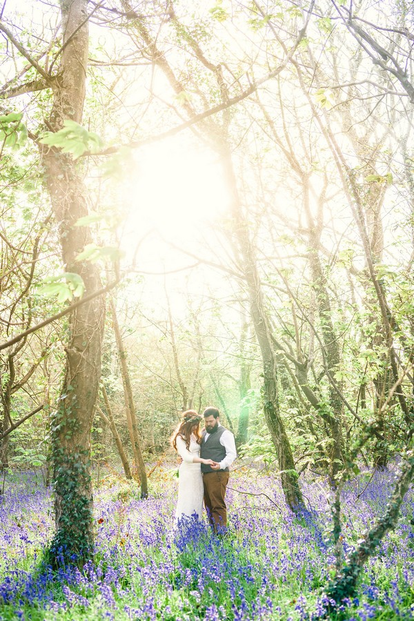 Bride and groom in woodland in hazy sunshine