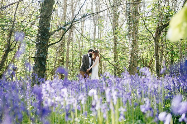 Bride and groom touching heads standing in bluebells