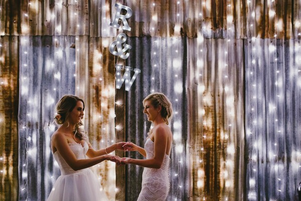 Brides facing each other holding hands