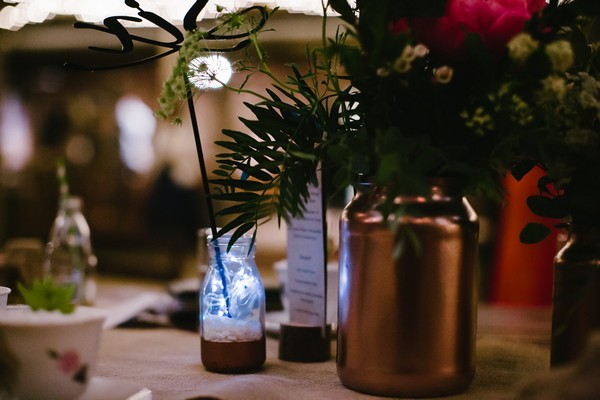 Copper vase and glass bottle table decor