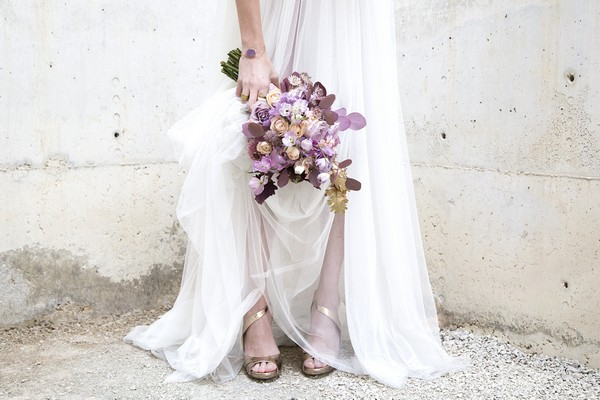 Bride's purple bouquet and gold shoes