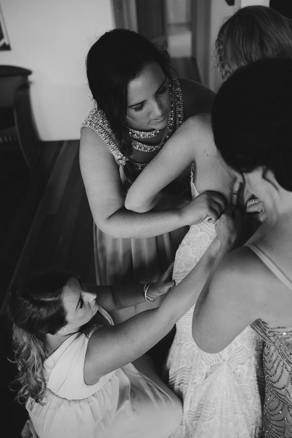 Bridesmaids helping bride get into wedding dress